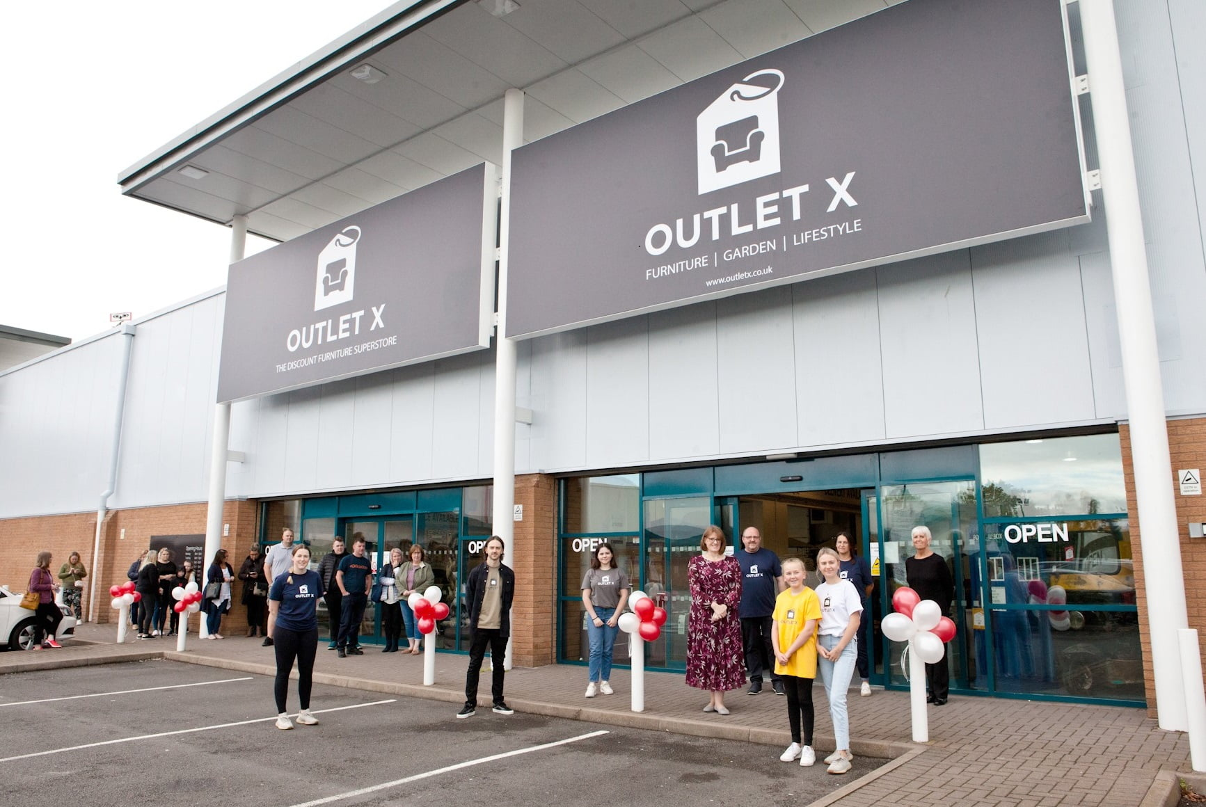 Liz Lowe, Head of Estates at Morris Property (centre in floral dress) with the Outlet X team and shoppers