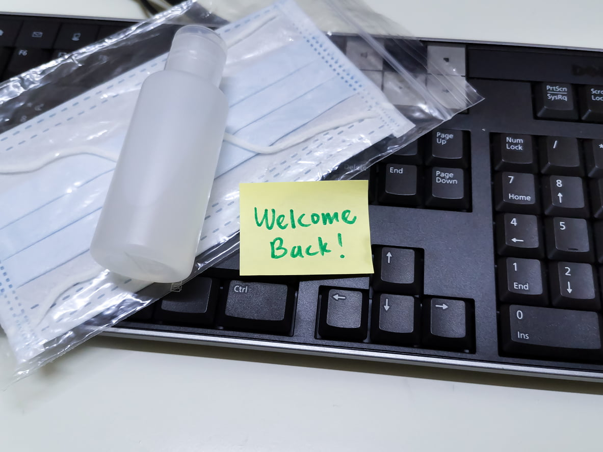 Welcome back note with hand sanitizer and mask on top of keyboard